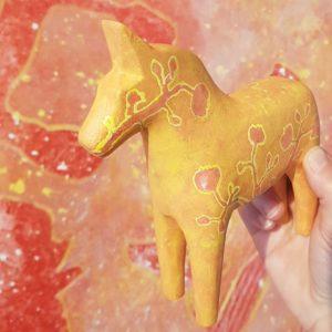 """Målad dalahäst på omålat lergods. Omålat lergods finns i min webbshop ifall du vill måla din egna variant. I bakgrunden syns min stora originalmålning """"Ingrid-Marie""""."""